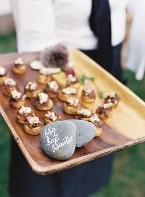 Cocktail hour appetizer on wood tray with rock calligraphy sign barbecue beef biscuits