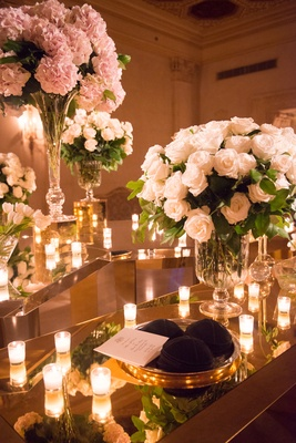 yarmulkes kippahs sitting on top of reflective table at jewish ceremony with candles and flowers