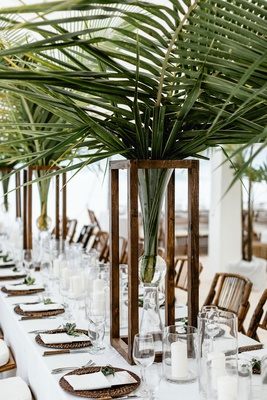 wedding reception on beach long table palm leaf centerpieces wood rattan tropical decor neutral