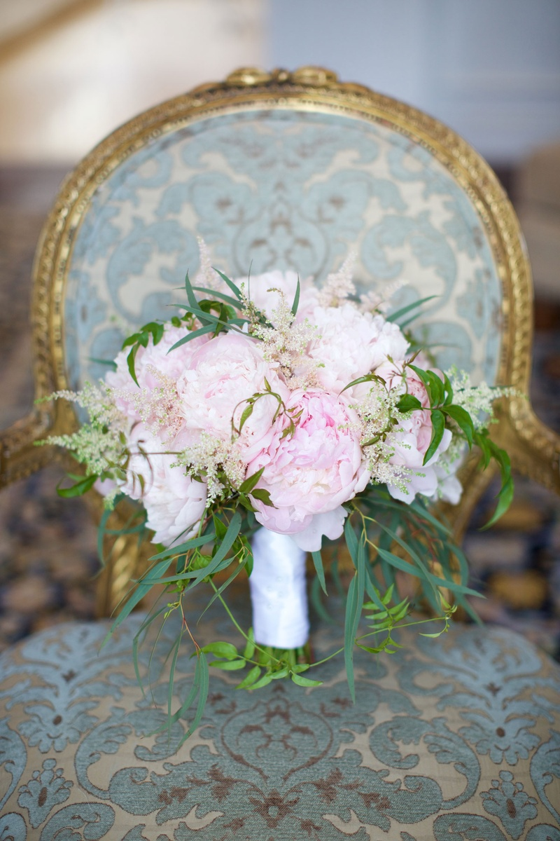 Bridal bouquet with greenery and fluffy pink peonies wrapped with white satin ribbon on chair