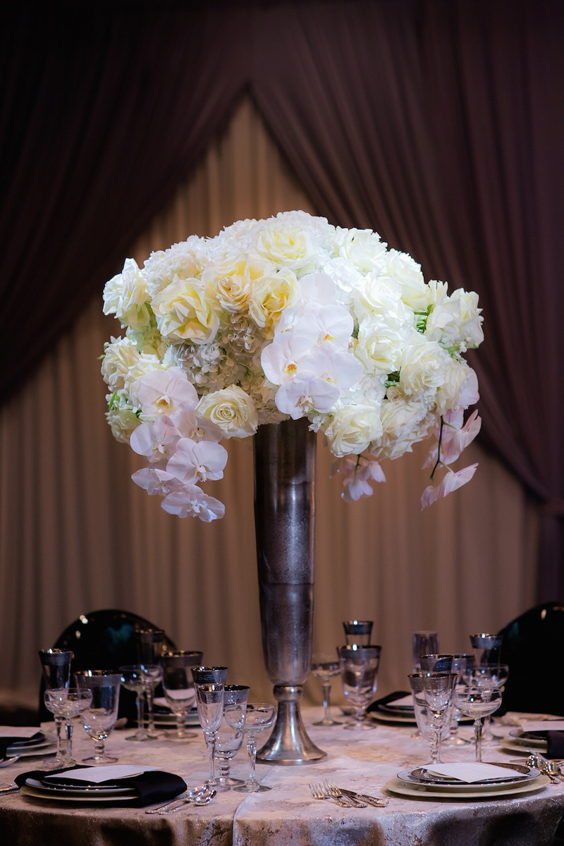 Wedding reception table with a tall silver vase, white orchids, roses, hydrangeas