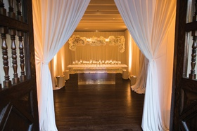 open doorway to reception with white drapery leading toward escort card table