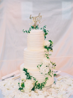wedding cake with buttercream fresh white flowers greenery gold happily ever after cake topper