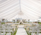 Seating in the round for outdoor tented wedding ceremony Huntington Beach, California flowers
