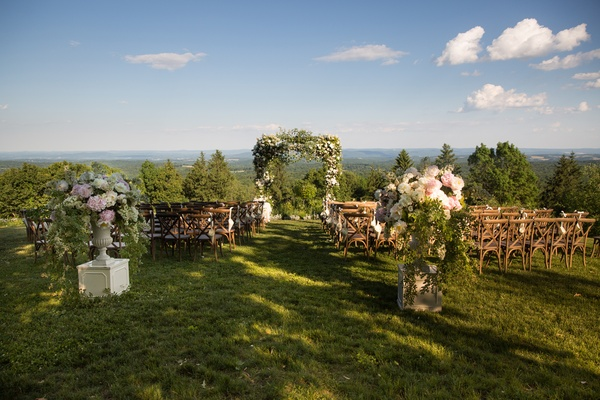 wedding ceremony arch with lots of greenery, wooden chairs, floral displays, forest views