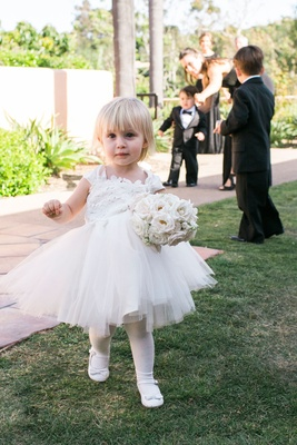 Flower girl in white dress tulle skirt with white tights leggings and shoes bouquet blonde hair