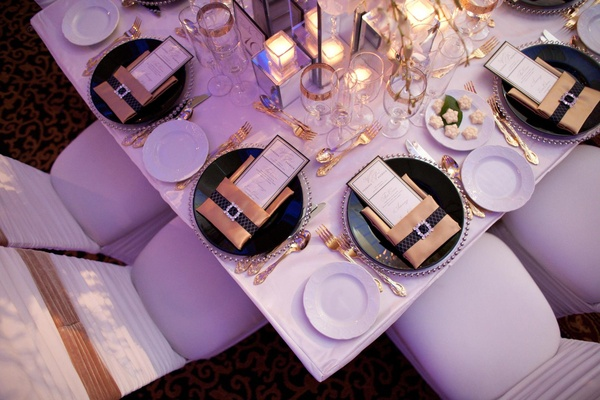 Wedding reception place settings with silver beaded chargers, black plates, and gold napkins