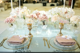 glass-top sweetheart table, dusty rose napkins, orchids, roses, gold flatware