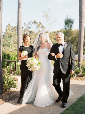 Bride in a line wedding dress veil over face walked down aisle by mother in black dress and father