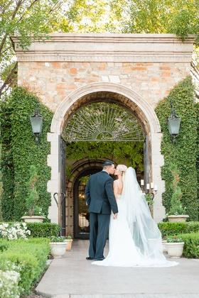 Bride and groom kiss during wedding portrait backs to camera tuxedo villa venue in Arizona wedding