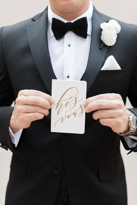 groom in tuxedo and bow tie white pocket square and boutonniere holding his vows calligraphy book