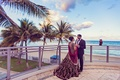 South Indian couple, bride in red wedding gown, bride in formal sari, groom in black tuxedo by beach