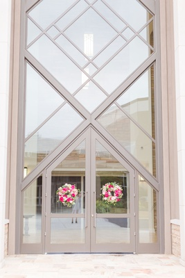 wedding ceremony tall church doors windows white and pink flowers greenery