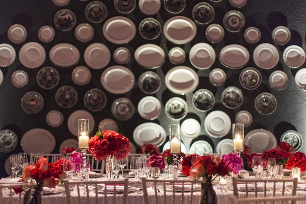 Wall of serving plates with rectangular wedding table