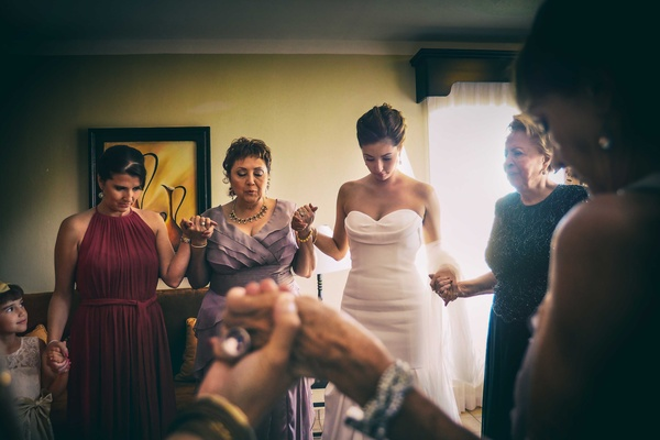 a bride and her female family members hold hands and pray before the traditional wedding ceremony