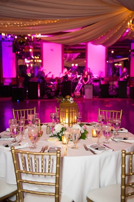 Round table with gold chairs and lantern next to dance floor