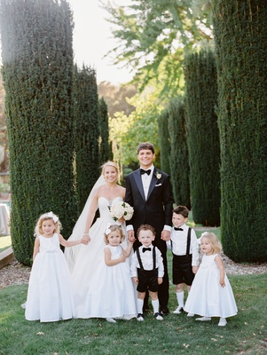 bride in martina liana ball gown, flower girls with bows in their hair, ring bearers with knee socks