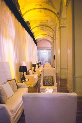 White wedding lounge furniture with metallic throw pillows, black lamps, and white drapery