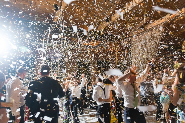 confetti falls over dancing guests at wedding reception