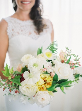 Bride in lace wedding dress holding bouquet of white flowers yellow flowers ferns greenery