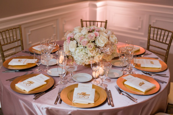 dusty rose linens, gold charger platers, low centerpiece of ivory and blush roses, gold chiavari ch