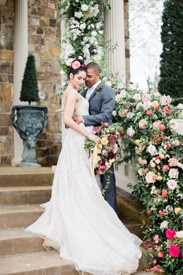 bride in beaded a-line wedding dress & groom in grey suit hugging next to floral bannister