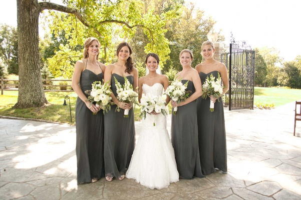 bride and bridesmaids in gray dresses with bouquets of white lilies flowers and green leaves foliage