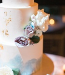 close up of wedding cake with gold foil and light blue water color details and fresh flowers