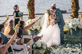 Bride and groom kissing amid cannon confetti