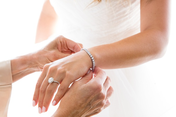 mother of the bride puts diamond tennis bracelet on bride