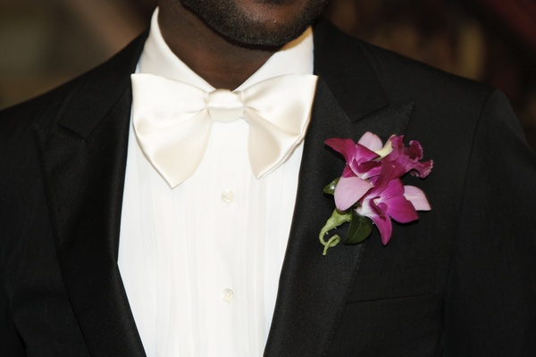 Groom in a black tuxedo, white bow tie, and a fuchsia orchid boutonniere