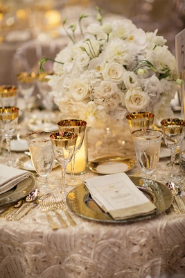 textured champagne linens, gold-rimmed goblets, white roses, orchids