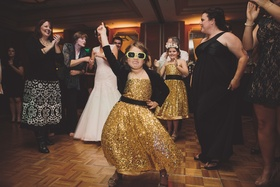 Young girl in gold glitter dress with sunglasses