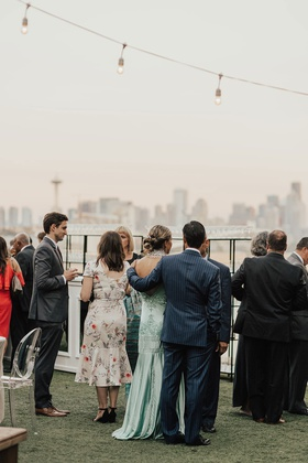 wedding cocktail hour guests enjoying mingling string bistro lights seattle skyline water