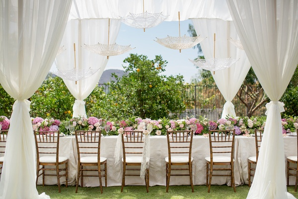 long table with white linen pink flower table runner drapery and parasols at pink bridal shower