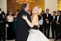 Bride in strapless ball gown from Kleinfeld BRidal with updo blonde hair dancing with father