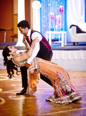Indian bride in choli and groom in tux on dance floor