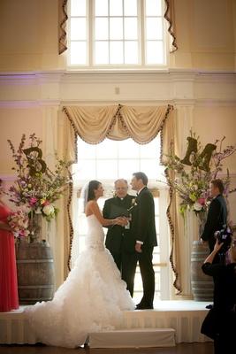 bride and groom at wine barrel altar