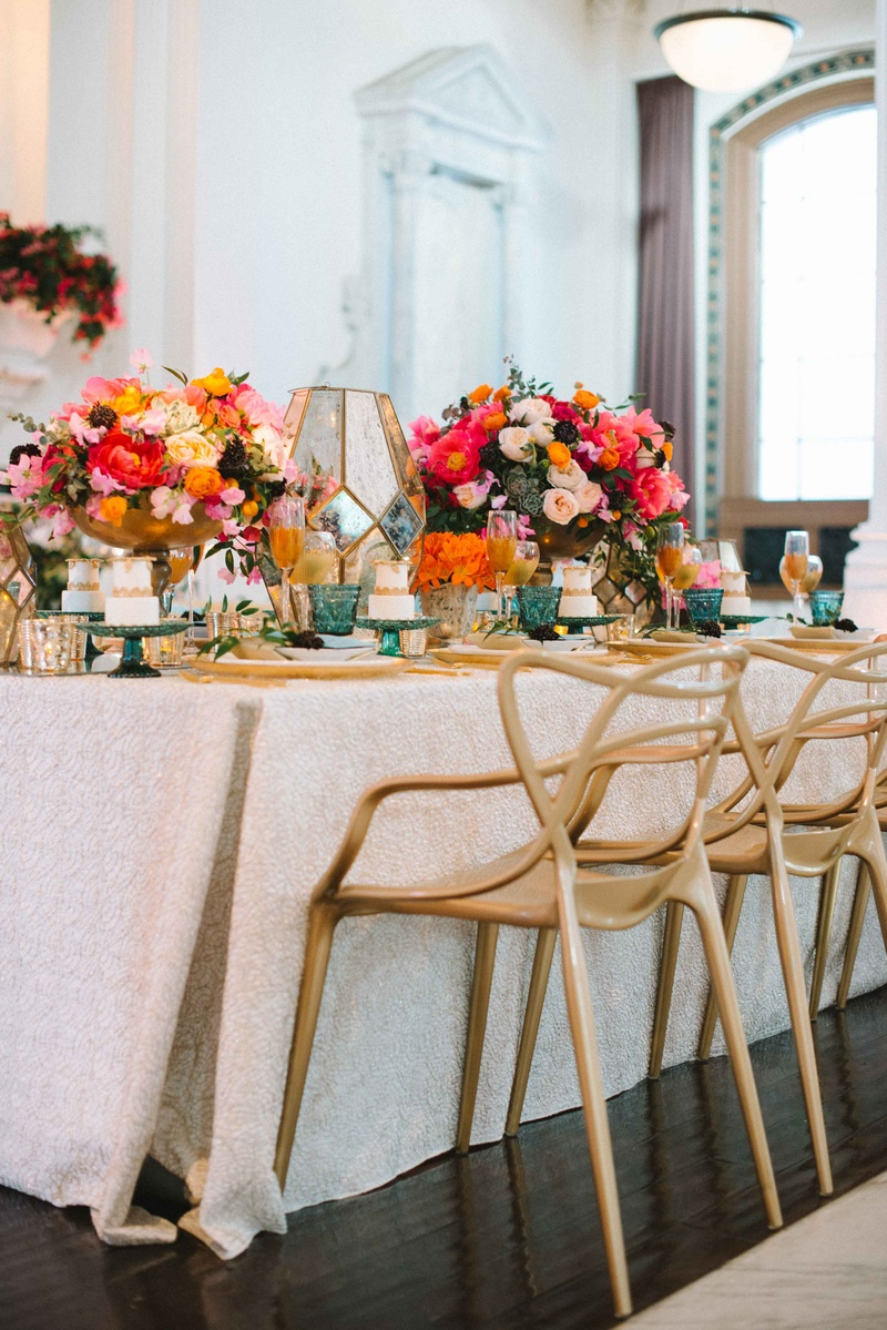 long tablescape gold chairs white table linen colorful flowers