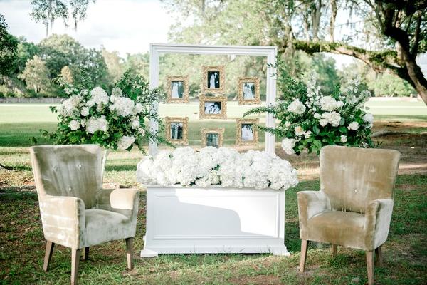 wedding reception cocktail hour white box white hydrangea velvet armchair white frame gold frames