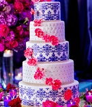 five tier wedding cake with layers of blue damask and ivory pincushion. Diamond bands, pink orchids