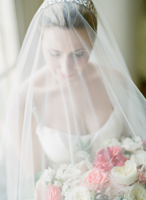 Bride in strap wedding dress scoop neck under veil with headband pink and white bouquet roses