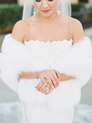 Bride in strapless romona keveza gown with chandelier earrings bracelet wedding ring french manicure