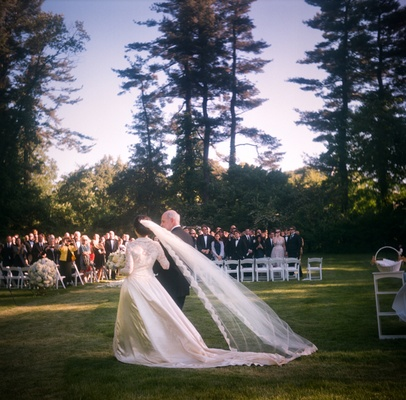 bride with long veil enters outdoor ceremony