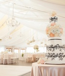Pink tablecloth over round table with black-and-white cake