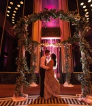 bride in elan, groom in armani without jacket, stand under round floral ceremony arbor