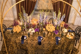 wedding styled shoot, blue delphiniums, light orange roses, purple sweet peas, black and gold linens