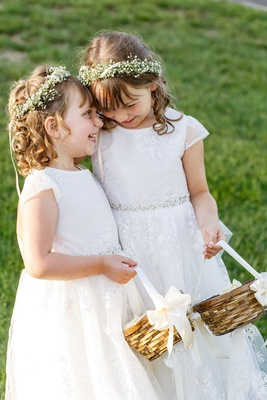 two flower girls with baby's breath flower crown, lace dresses, baskets, laughing together