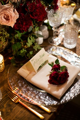 Green calligraphy on place card at head table clear charger plate gold rim flatware greenery and red