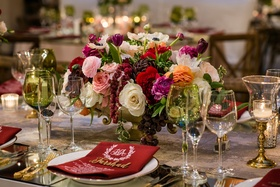 Low wedding centerpiece green glassware white red pink orange flowers monogram menu burgundy napkin